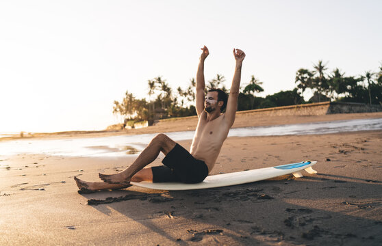 Young surfer stretching while sitting on surfboard