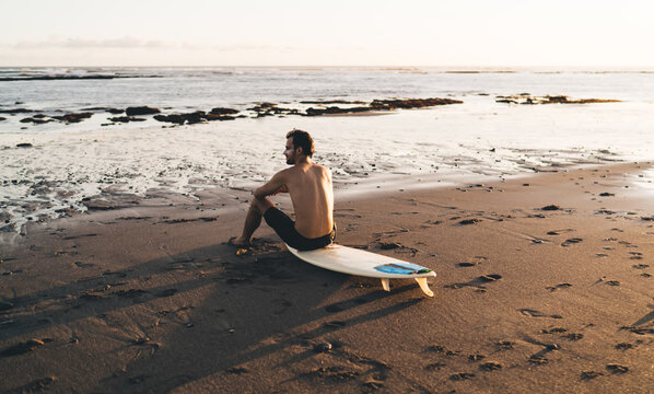 Male surfer relaxing on beach and looking at sea waves