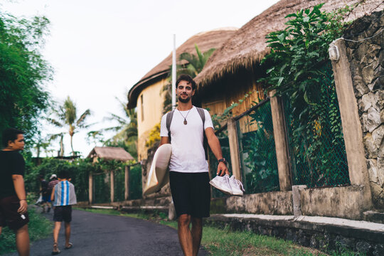 Cheerful surfer walking on road with surfboard in summer