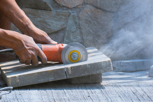 Close up of worker hand using grinder cutting stone tile floor for paving pavement job