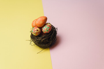 Many easter eggs on trendy pink and yellow pastel background. Decorative small eggs in a nest of...