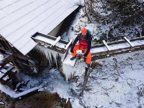 cool male Hiker with beard, with backpack, orange cap and orange pants is next to icy stream and water wheel surrounded by icicles and snow in winter in austria
