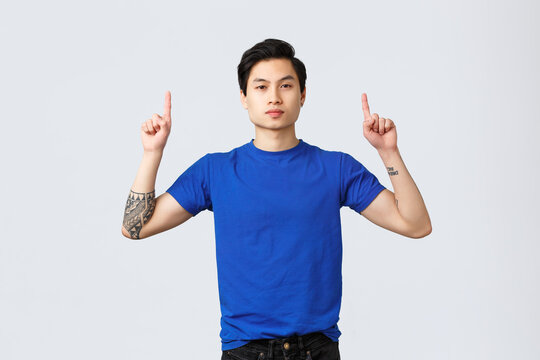 Different emotions, people lifestyle and advertising concept. Confident, serious asian man in blue t-shirt with tattoos, pointing fingers up, inform clients, showing way to banner, grey background