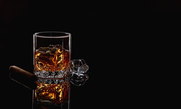 Whiskey with ice or brandy in glass with cigar on black background. Whisky with ice in glass. Whiskey or brandy. Selective focus.