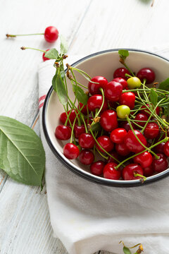Close up of  cherries in enamel bowl on rustic table