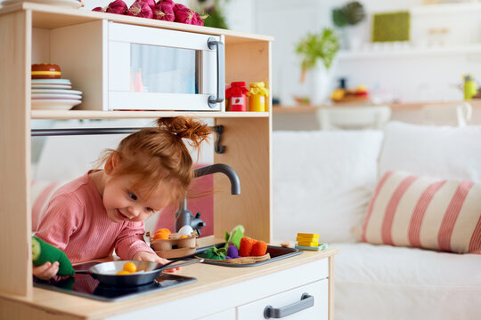 funny toddler baby girl playing on toy kitchen at home
