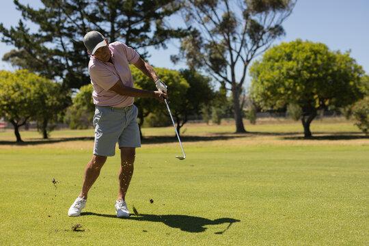 Caucasian senior man holding golf club taking a shot on the green