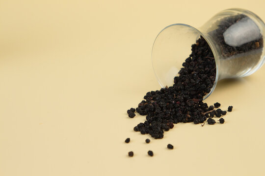 Dried elderberries in a transparent glass on a light yellow background. Elderberry contains zinc and antioxidants that boost immune function and suppress colds and flu.