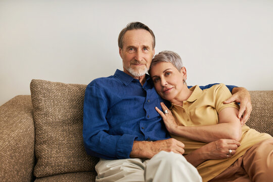 Senior couple embracing on a sofa. Affectionate people hugging at home.