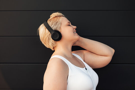 Plus size woman listening to music near a black wall. Young curvy female taking a break during exercises.