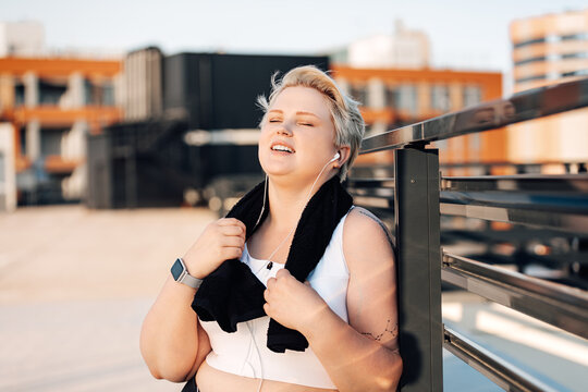 Smiling woman with plus size body holding a towel relaxing after workout