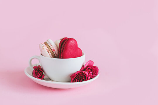 Tasty french macaroons with pink roses in a white cup. Heart-shaped macaron. Pink pastel background.