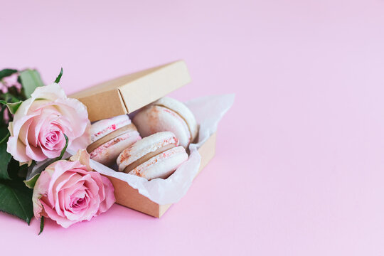 Tasty french macaroons in a box with pink roses on a pink pastel background.