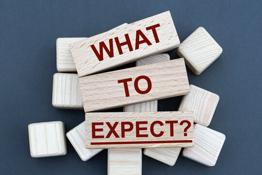 WHAT TO EXPECT? - words on wooden bars on cubes on a gray background