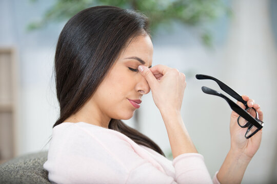 woman holding eyeglasses and rubbing the bridge of her nose