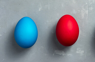 Blue and red Easter eggs on textured gray background. Horizontal orientation. Top view.