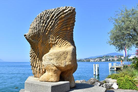 Montreux, Switzerland- August 24, 2019. Stone sculpture of a fish with human legs on Leman (Geneva) lakeshore, Montreux Riviera, Switzerland.