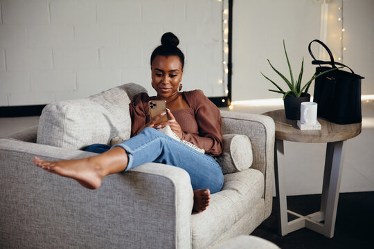 Black woman relaxing and comfortable on couch looking at cellphone