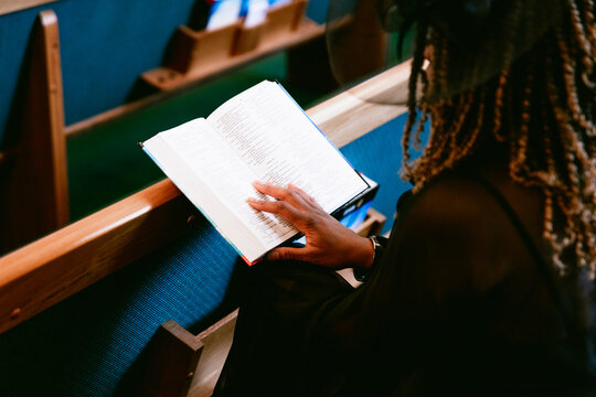 Woman sitting in pews and reading bible at church