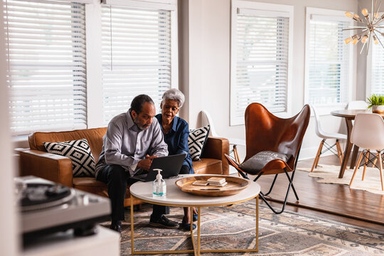 Retired senior couple checking messages on laptop at home