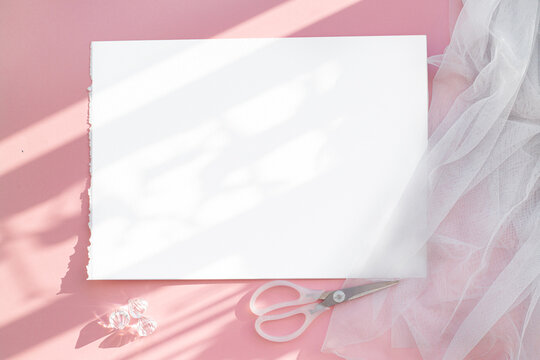A blank layout of a white frame on an abstract pink table. Grey tulle fabric under the sheet. The light from the sun creates patterns. Delicate luxury and airy background. Scissors and transparent cry