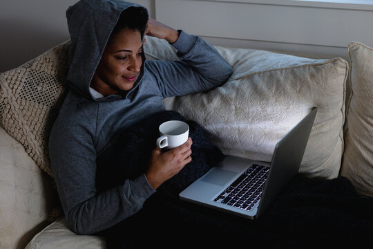 Mature woman snuggled on couch on laptop