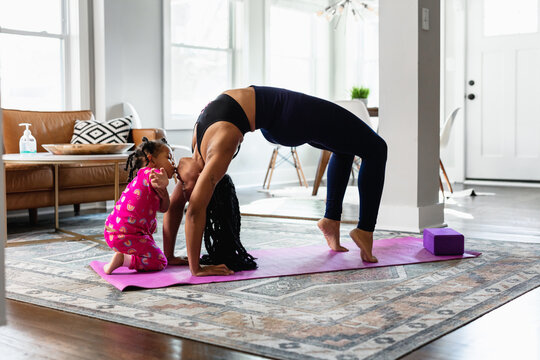 Moment when daughter kiss mother while she does yoga exercise at home