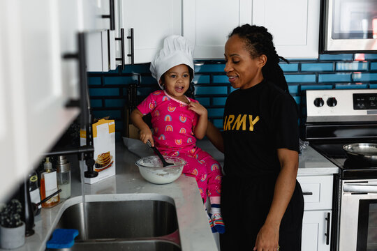 Mother and daughter cook breakfast pancakes in kitchen
