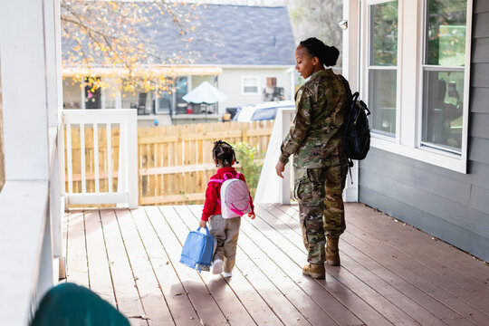 Military woman walks daughter to school