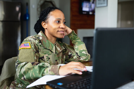 Happy military woman listening to family while working from home at laptop