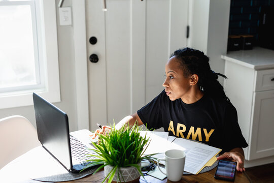Military woman works remotely at home with laptop