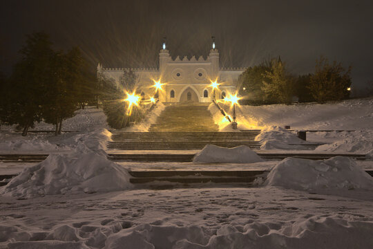 Snow-covered stairs in front of the Lublin Castle illuminated by lanterns