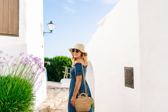 Female tourist wearing sunglasses and hat looking over shoulder while standing in Binibeca village, Minorca, Spain