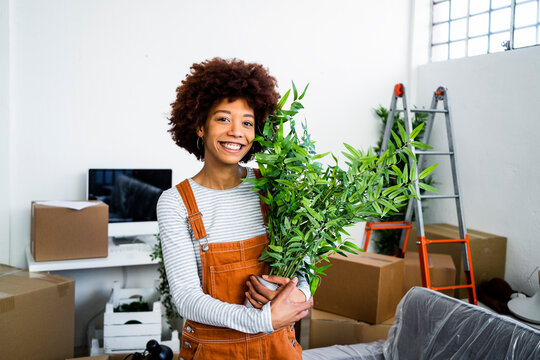 Happy afro woman holding potted plant during relocation in new apartment