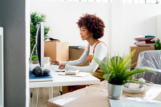 Afro woman using computer while surrounded by cardboard boxes in new home