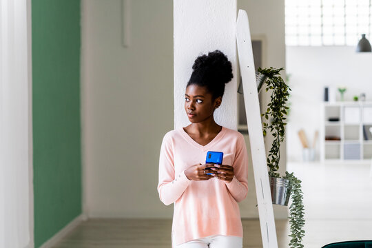 Thoughtful woman with mobile phone looking away while standing at home