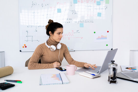 Young female student with headphones studying on laptop