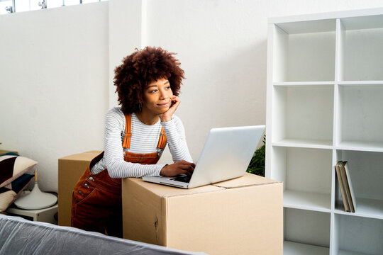 Afro woman with hand on chin day dreaming while standing by laptop in new loft apartment