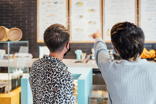 Woman wearing face mask pointing at menu while standing by friend at restaurant