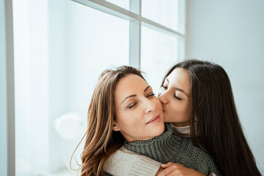 Daughter kissing mother on cheek by window at home