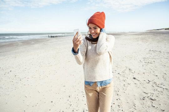 Portrait of woman wearing knit hat talking on smart phone at beach