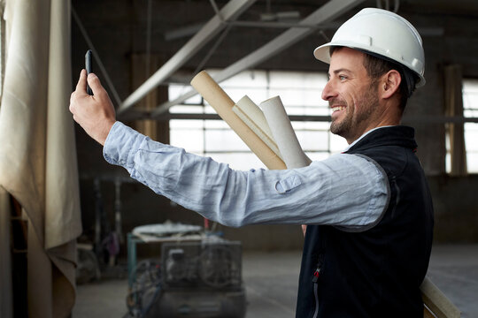 Smiling male architect video calling over smart phone while standing in building