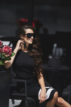 Outdoor summer portrait of a model woman wearing trendy sunglasses and fashionable dress sitting at the cafe table in the street of a European city