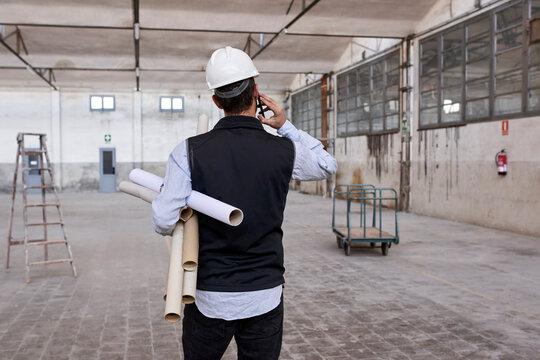 Male architect holding cardboards talking over mobile phone while standing in building