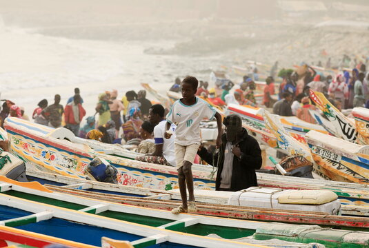 A boy jumps over pirogues as dust carried by winds from the Sahara Desert shrouds Dakar