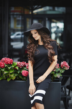 A fashionable young woman in trendy sunglasses and stylish dress sitting at the cafe table outdoors
