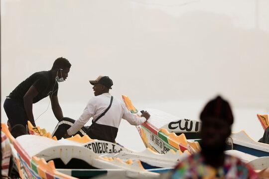 Men talk as dust carried by winds from the Sahara Desert shrouds Dakar