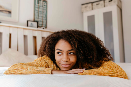 Thoughtful woman smiling while lying on bed at home