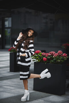 Cheerful model woman with perfect body and long sexy legs in a modish outfit and black hat posing on the European city street