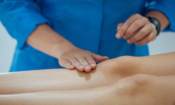 Mãos sobre perna de paciente em massagem